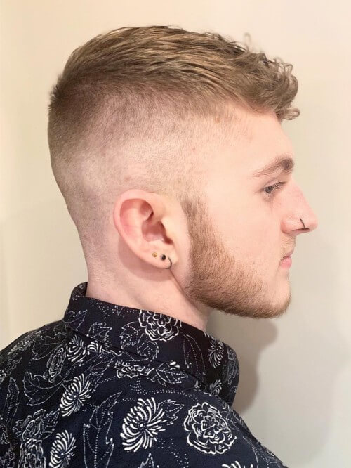 short curly fade hairstyle with bald skin fade side part haircut